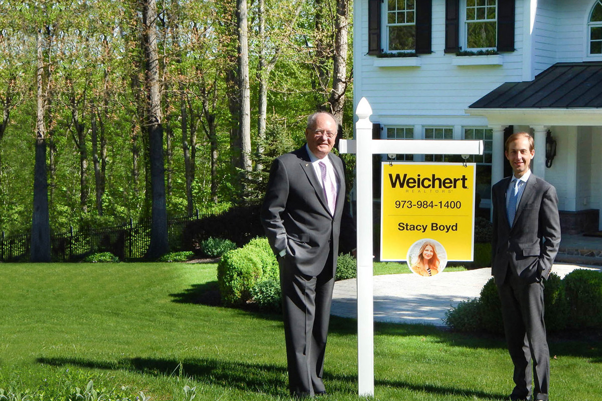 Jim Weichert and James Weichert standing by a Weichert property sign